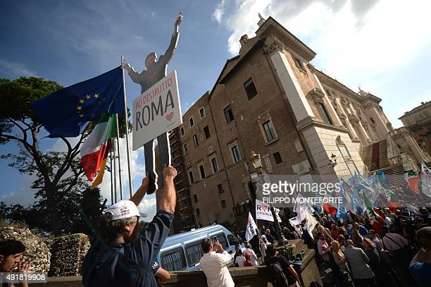 A man holds a placard with a picture of Rome's mayor Ignazio Marino reading 'I destroyed Rome' as they ask for his resignation on October 8 2015...