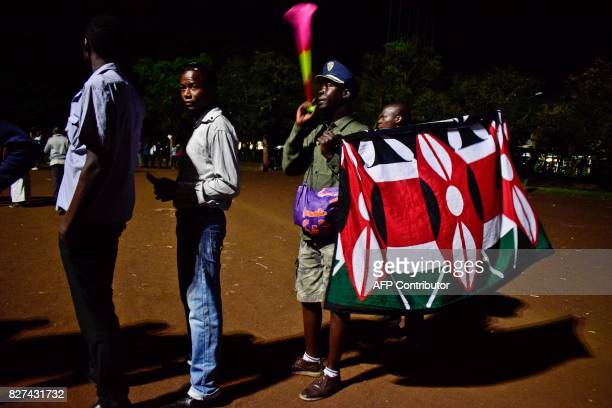 A man holds a plastic horn and a flag with the national colours of the Kenyan flag as Kenyans wait in line to cast their ballot in the general...