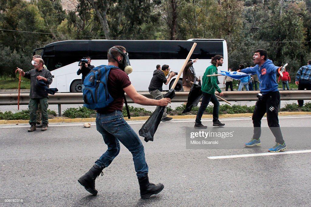A man holds a poll as clashes break out on the highway after police blocked the road from a planned pension reform protest outside the Agriculture ministry on February 12, 2016 in Athens, Greece. Around reportedly 800 protesters from Crete gathered outnumbering police who were armed with teargas.