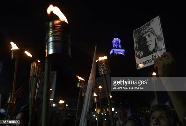 A man holds a portrait during a march with torches demanding the release of the leader of the Tupac Amaru neighbourhood association activist Milagro...