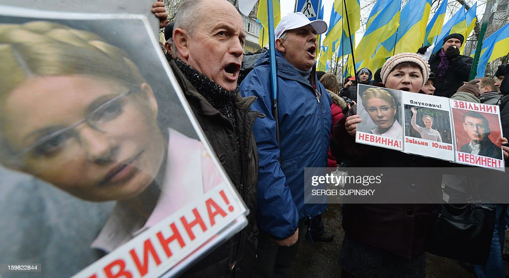 A man holds a portrait of jailed former Ukrainian prime minister Yulia Tymoshenko reading 'Not Guilty!' during a rally organized by the opposition in front of the President's office in Kiev on January 21, 2013. Prosecutor General Viktor Pshonka on Friday accused Ukraine's jailed former prime minister Yulia Tymoshenko of organising the 1996 murder of a powerful lawmaker and warned that a guilty verdict could put her behind bars for life. The prosecutor said the fiery 52-year-old has been informed by prosecutors that she and another former prime minister detained in the United States are formal suspects in the murder of deputy Yevgen Shcherban.