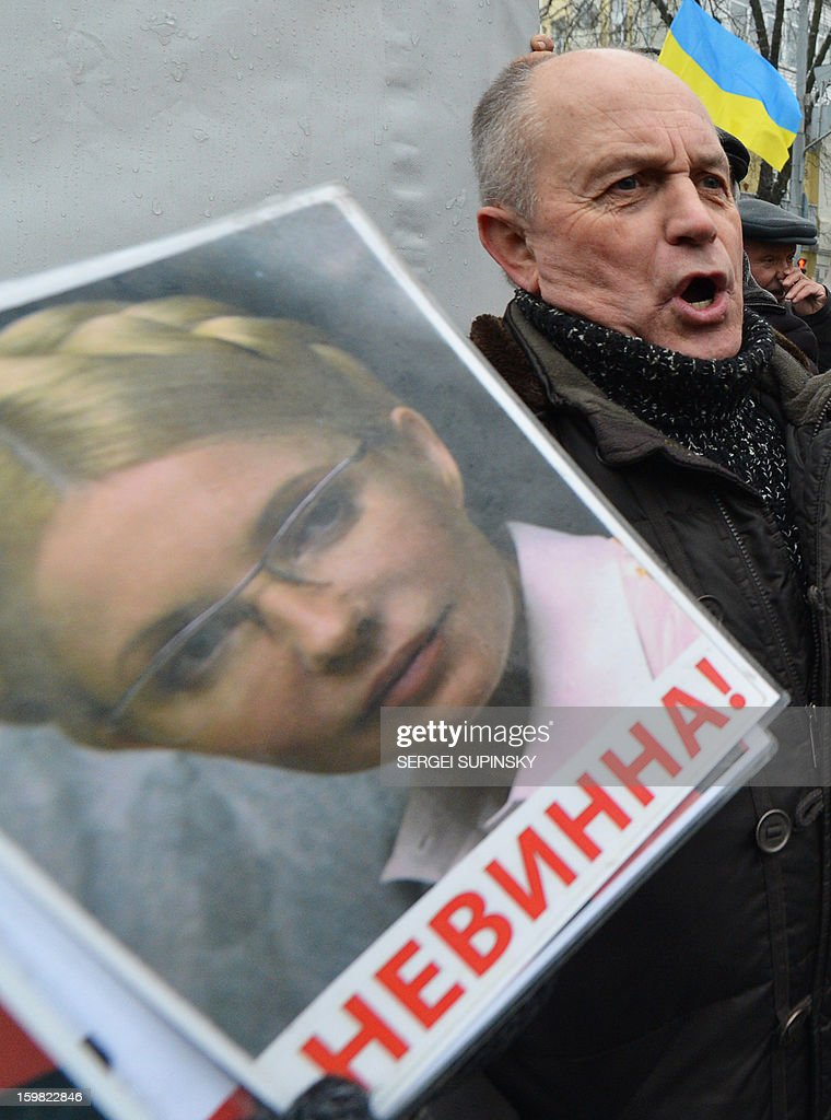 A man holds a portrait of jailed former Ukrainian prime minister Yulia Tymoshenko reading 'Not Guilty!' during a rally organized by the opposition in front of the President's office in Kiev on January 21, 2013. Prosecutor General Viktor Pshonka on Friday accused Ukraine's jailed former prime minister Yulia Tymoshenko of organising the 1996 murder of a powerful lawmaker and warned that a guilty verdict could put her behind bars for life. The prosecutor said the fiery 52-year-old has been informed by prosecutors that she and another former prime minister detained in the United States are formal suspects in the murder of deputy Yevgen Shcherban. AFP PHOTO/ SERGEI SUPINSKY