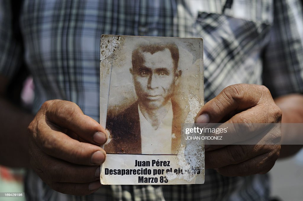 A man holds a portrait of Juan Perez disappeared during the internal armed conflict during a protest against the quashing of the 80year sentence for...