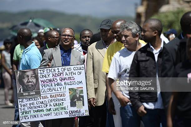 A man holds a portrait of Nelson Mandela as people queue to bid farewell to South African former president Nelson Mandela lying in state outside the...
