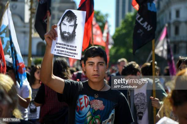 A man holds a portrait of Santiago Maldonado a missing activist who disappeared two months ago during a police operation in Chubut and whose body is...
