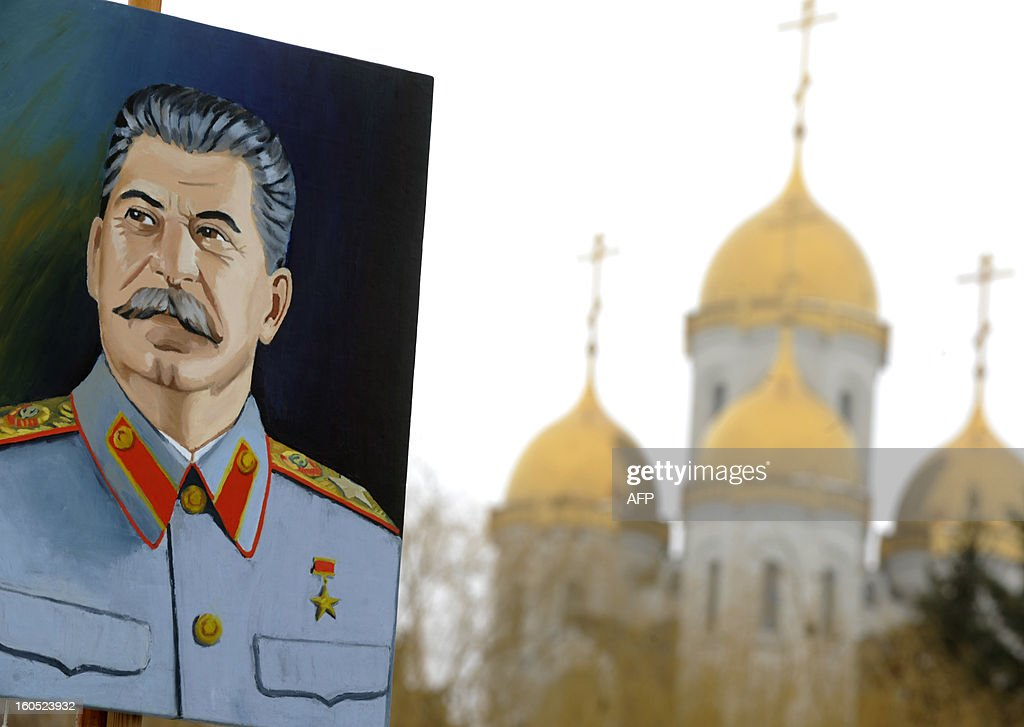 A man holds a portrait of the Soviet dictator Josef Stalin against an Orthodox cathedral at the memorial built to honour those who died in the Battle of Stalingrad during the World War II, in the Russian city of Volgograd, formerly Stalingrad, on February 2, 2013. Russia marked today the 70th anniversary of a brutal battle in which the Red Army defeated Nazi forces and changed the course of World War II. The pulverised city was renamed Volgograd in 1961 after Soviet leaders admitted the extent of Stalin's tyranny during his decades in power.