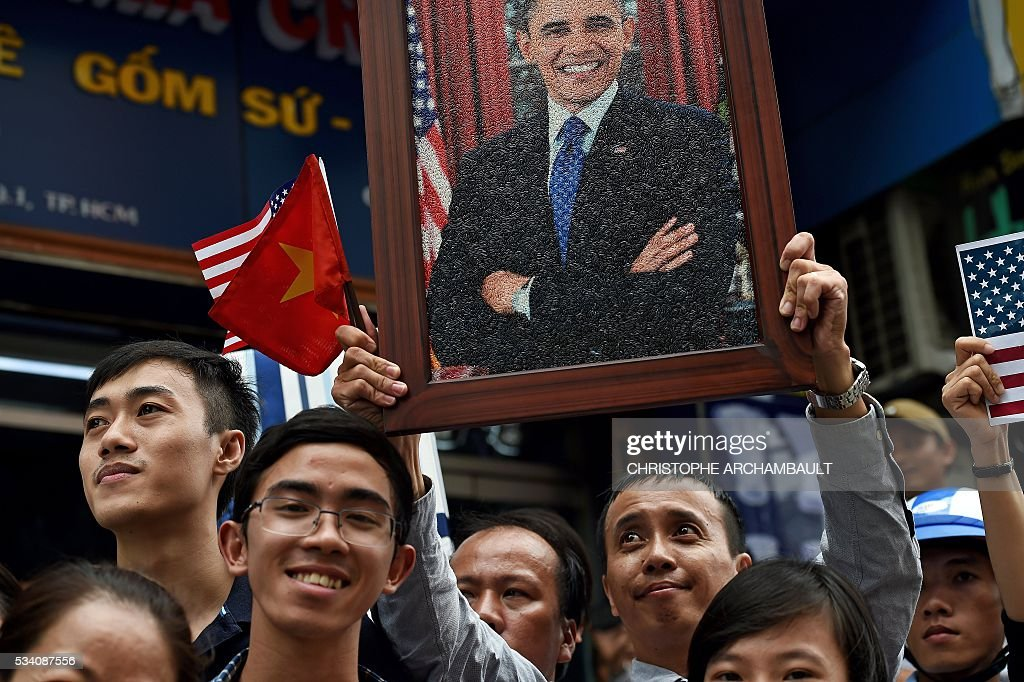 A man holds a portrait of US President Barack Obama as people line up the streets to catch a glimpse of the US leader on his way to the airport at the end of two-day visit to Ho Chi Minh City on May 25, 2016. Obama fielded questions on May 25 on everything from rap and weed smoking to leadership and his good looks at a lively town hall-style meeting with young Vietnamese, who say the US leader is a far cry from their staid Communist rulers. / AFP / CHRISTOPHE
