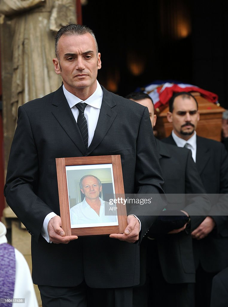 A man holds a portrait on January 31, 2013 of French citizen Yann Desjeux, 53, killed in the hostage rescue operation at a remote gas plant in In Amenas that was seized by Islamist militants, at the end of his funeral at the Saint-Andre church in Bayonne, southwestern France.
