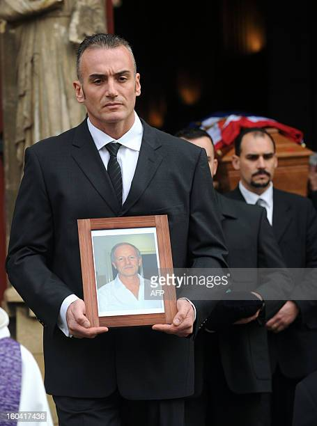 A man holds a portrait on January 31 2013 of French citizen Yann Desjeux killed in the hostage rescue operation at a remote gas plant in In Amenas...