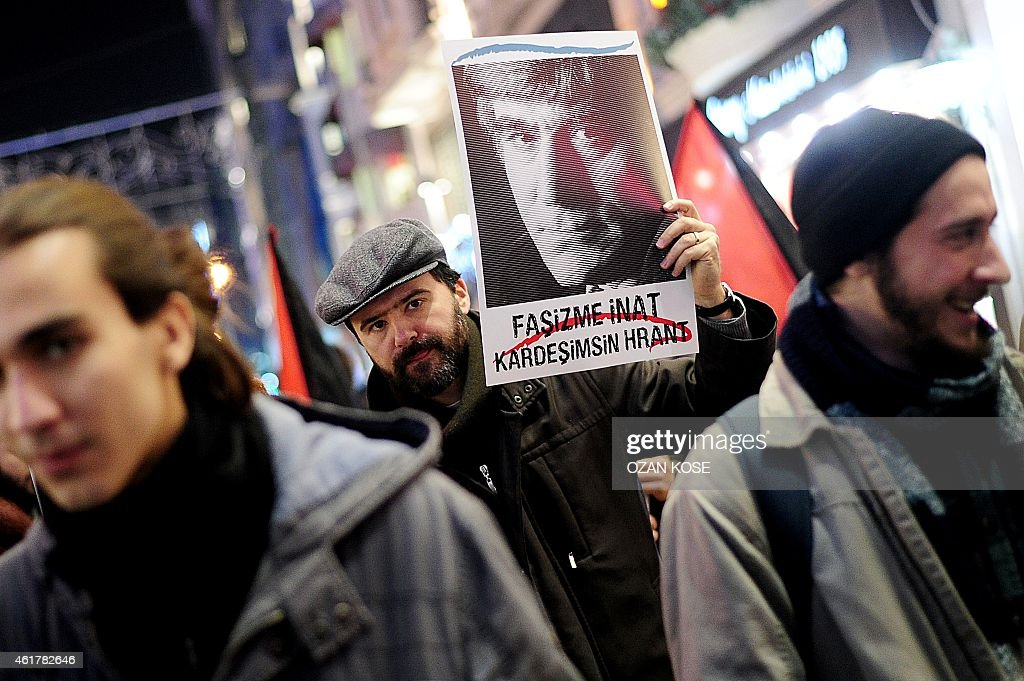 A man holds a poster depicting slain journalist <a gi-track='captionPersonalityLinkClicked' href=/galleries/search?phrase=Hrant+Dink&family=editorial&specificpeople=741548 ng-click='$event.stopPropagation()'>Hrant Dink</a> and reading 'Despite fascism Hrant is our brother' during a march in memory of Dink, on Istiklal avenue in Istanbul on January 19, 2015. Turkish riot police were out in force as large crowds massed in Istanbul to demand justice for a prominent Turkish Armenian journalist murdered eight years ago. <a gi-track='captionPersonalityLinkClicked' href=/galleries/search?phrase=Hrant+Dink&family=editorial&specificpeople=741548 ng-click='$event.stopPropagation()'>Hrant Dink</a>, one of the most prominent voices of Turkey's shrinking Armenian community, was killed by a gunman on January 19, 2007. The 52-year-old Dink, a prominent member of Turkey's tiny Armenian community, campaigned for reconciliation but was hated by Turkish nationalists for calling the World War I massacres of Armenians a genocide. AFP PHOTO /OZAN KOSE