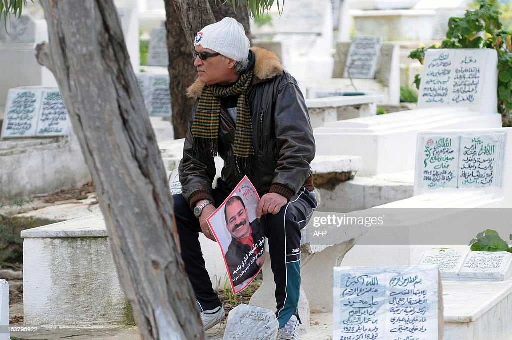 A man holds a poster featuring the late anti-Islamist opposition leader Chokri Belaid during a gathering at his tomb to mark the 40th day of mourning after his death at El-Jellaz cemetery in a suburb of Tunis on March 16, 2013. Belaid was gunned down outside his Tunis home on February 6, with the broad daylight killing sparking clashes between protesters and police and prompting the largest anti-government demonstrations since the revolution.