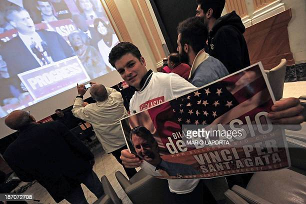 A man holds a poster of Bill de Blasio as others look at on a giant screen at the electoral support committee office of Bill de Blasio the speech of...