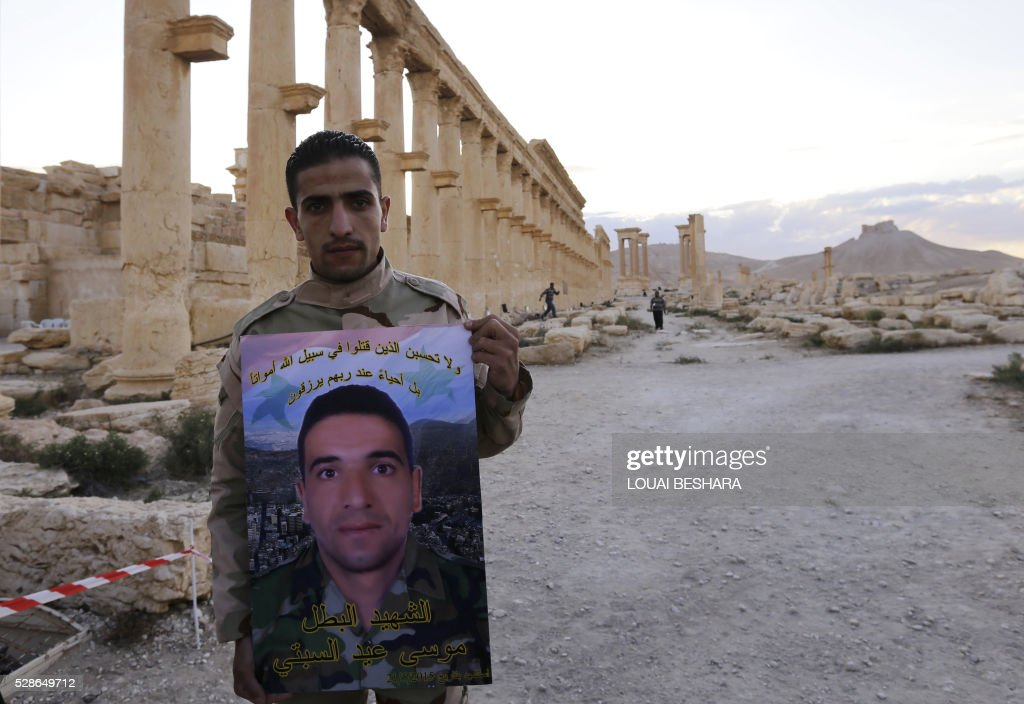A man holds a poster bearing a portrait of a fighter during a visit to the historical site of the ancient theatre of Syria's ravaged Palmyra on May 6, 2016 ahead of a music concert following its recapture by regime forces from the Islamic State group fighters. Syrian troops backed by Russian air strikes and special forces on the ground recaptured UNESCO world heritage site Palmyra from Islamic State (IS) group fighters in March 2016. BESHARA
