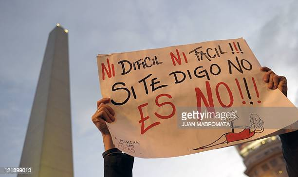 A man holds a poster reading 'Neither Hard Nor Easy If I Say No It's No' during the worldwide 'Slutwalk' against sexual violence in Buenos Aires on...