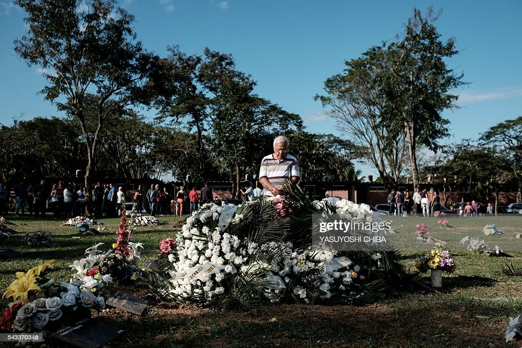 A man holds a prayer after the funeral of Gisele Palhares Gouvea, in Rio de Janeiro, Brazil, on June 27, 2016. Brazilian 34-year-old doctor Gisele Palhares Gouvea was shot in the head inside her SUV on June 27 as she drove home after attending the inauguration of the service center for handicapped people in northern Rio de Janeiro. / AFP / YASUYOSHI