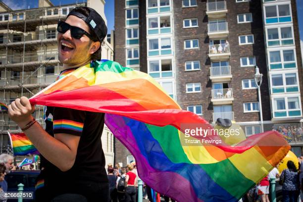 A man holds a Pride flag during the annual Brighton Pride Parade And Festival on August 5 2017 in Brighton England