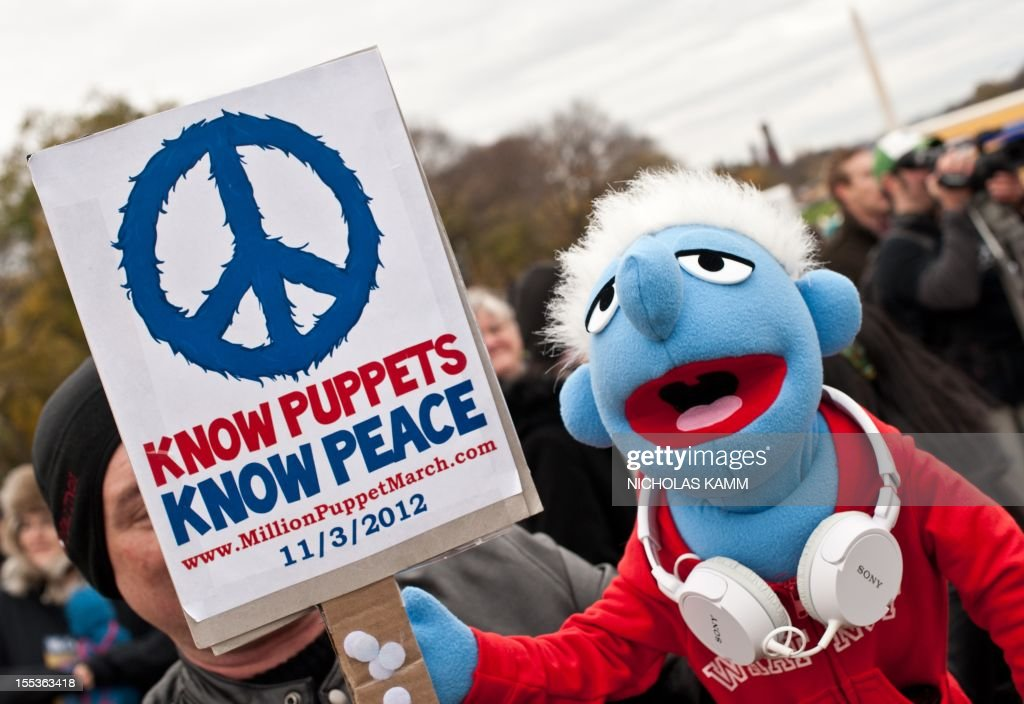A man holds a puppet and a sign in support of public broadcasting during the 'Million Puppet March' in Washington on November 3, 2012. Several hundred supporters of US public broadcasting in a good-humored protest prompted by US Republican candidate Mitt Romney's threat, in a televised debate with President Barack Obama a month ago, to halt government funding to public media if he wins the White House on ovember 6. AFP PHOTO/Nicholas KAMM