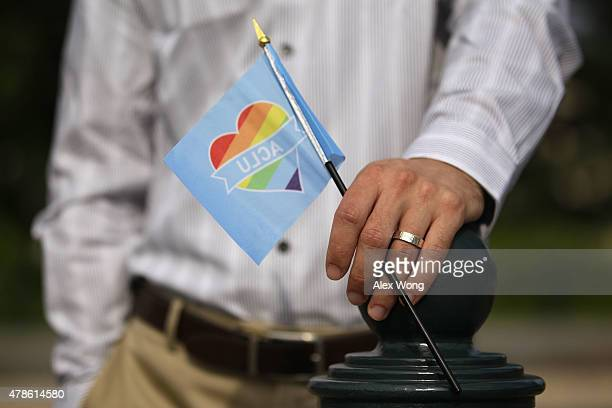 A man holds a rainbow flag in support of samesex marriage outside the US Supreme Court June 26 2015 in Washington DC The high court ruled that...