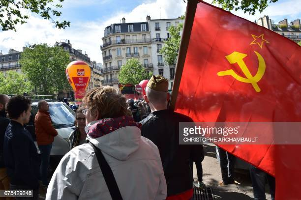 A man holds a red flag with the communist symbol of the hammer and sickle during a march for the annual May Day workers' rally in Paris on May 1 2017...