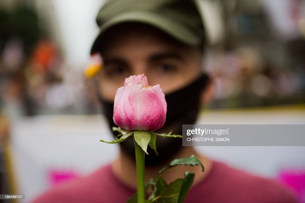 A man holds a rose during a silent demonstration against police violence along the streets of Rio de Janeiro, Brazil on October 31, 2013.