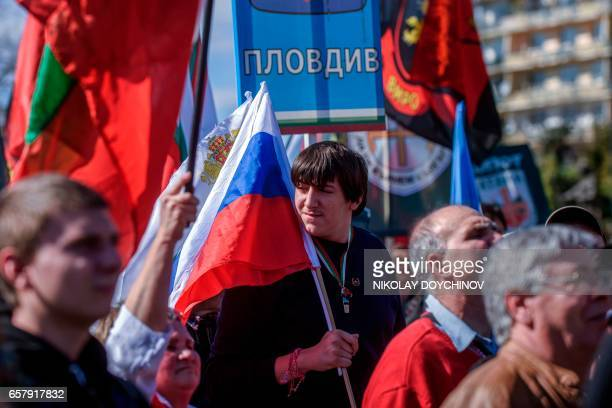 A man holds a Russian flag during a political rally on Bulgaria's National Day in central Sofia on March 3 2017 Member of NATO since 2004 and of the...