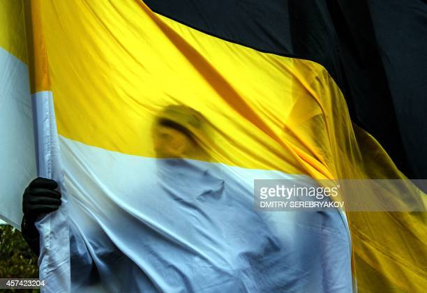 A man holds a Russian imperial flag as he takes part in a rally in support of the selfproclaimed 'People's Republics' of Donetsk and Lugansk in...