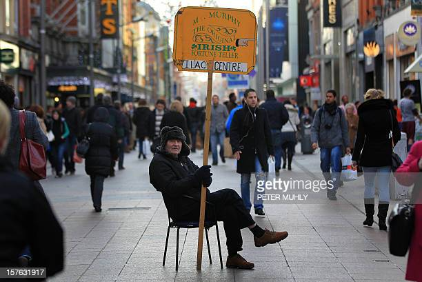 A man holds a sales board promoting the services of an 'Irish Fortune Teller' in the O'Connell Street shopping district as pedestrians walk past...