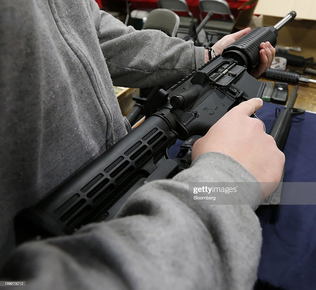 A man holds a semi-automatic assault rifle at the Rocky Mountain Gun Show in Sandy, Utah, U.S., on Saturday, Jan. 5, 2013. A working group led by Vice President Joe Biden is seriously considering measures that would require universal background checks for firearm buyers, track the movement and sale of weapons through a national database, strengthen mental health checks and stiffen penalties for carrying guns near schools or giving them to minors. Photographer: George Frey/Bloomberg via Getty Images