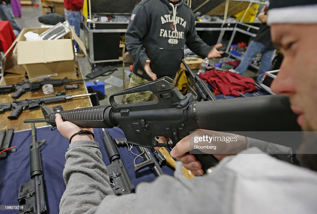 A man holds a semi-automatic assault rifle made by Bushmaster Firearms International LLC at the Rocky Mountain Gun Show in Sandy, Utah, U.S., on Saturday, Jan. 5, 2013. A working group led by Vice President Joe Biden is seriously considering measures that would require universal background checks for firearm buyers, track the movement and sale of weapons through a national database, strengthen mental health checks and stiffen penalties for carrying guns near schools or giving them to minors. Photographer: George Frey/Bloomberg via Getty Images