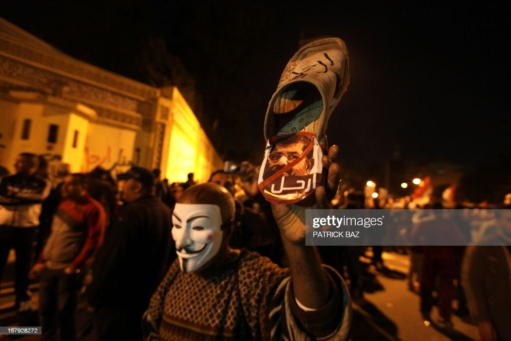 A man holds a shoe with the face of Egyptian President Mohamed Morsi as thousands of opponents to Morsi gather in front of the presidential palace on December 7, 2012 in Cairo. Thousands of protesters broke through a barbed-wire perimeter protecting Morsi's palace, as his vice-president hinted at a possible compromise aimed at calming the seething crisis dividing Egypt. AFP PHOTO/PATRICK BAZ