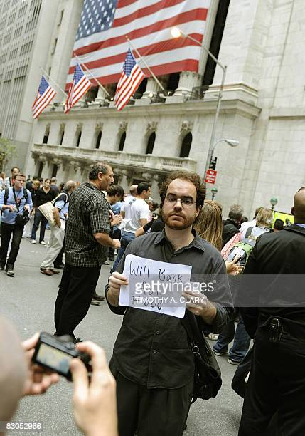 A man holds a sigh up outside the New York Stock Exchange September 29 2008 as The Dow Jones Industrial Average sank 77059 points percent to 1037254...