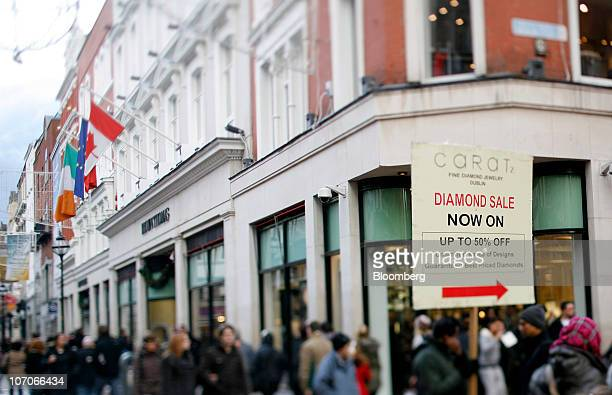 A man holds a sign advertising a diamond sale while standing on Grafton Street in Dublin Ireland on Sunday Nov 21 2010 Ireland sought international...