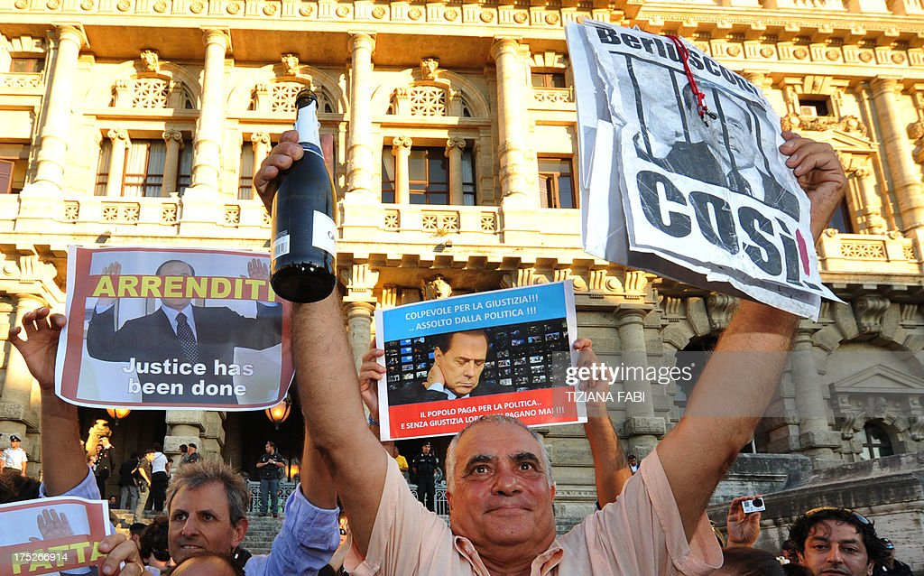 A man holds a sign and a champagne bottle as people celebrate the Italian Supreme Court's sentencing of Italian politician Silvio Berlusconi, in front of the Cassation building in Rome, on August 1, 2013. Italy's top court today confirmed a prison sentence for former prime minister Silvio Berlusconi in the first ever definitive conviction in a tumultuous career for the billionaire tycoon. The court upheld a tax fraud sentence of four years in prison of which three years are covered by an amnesty, even though Berlusconi is certain to be granted community service or house arrest instead.