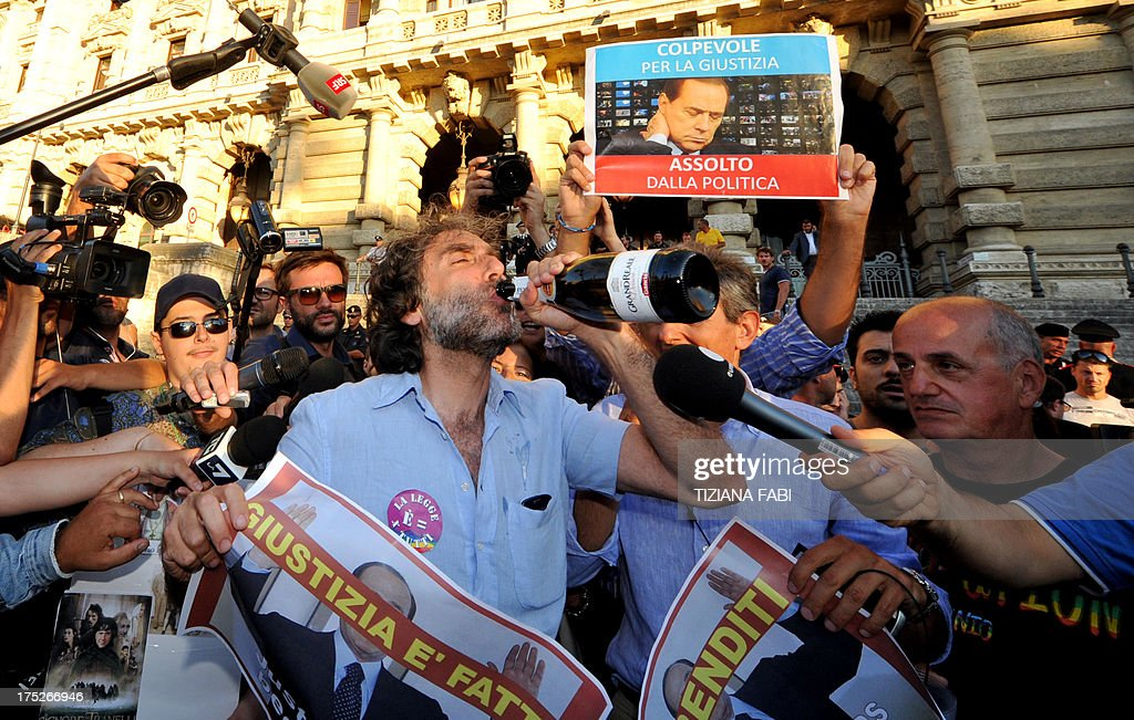 A man holds a sign and drinks from a champagne bottle as people celebrate the Italian Supreme Court's sentencing of Italian politician Silvio Berlusconi, in front of the Cassation building in Rome, on August 1, 2013. Italy's top court today confirmed a prison sentence for former prime minister Silvio Berlusconi in the first ever definitive conviction in a tumultuous career for the billionaire tycoon. The court upheld a tax fraud sentence of four years in prison of which three years are covered by an amnesty, even though Berlusconi is certain to be granted community service or house arrest instead.