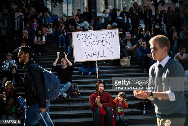 A man holds a sign as he takes part in a demonstration in solidarity with migrants seeking asylum in Europe after fleeing their home countries in...