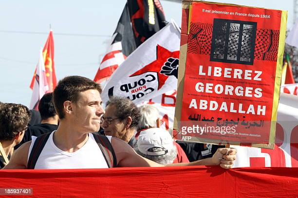 A man holds a sign as he takes part in a protest calling for the liberation of Lebanese activist Georges Ibrahim Abdallah in front of the French...