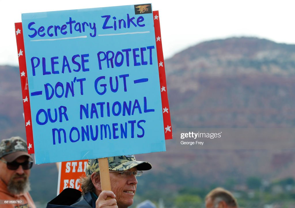 A man holds a sign as he waits at the Kanab Airport to protest U.S. Secretary of the Interior Ryan Zinke on May 10, 2017 in Kanab, Utah. Zinke has been in the state of Utah since Sunday talking with state and local officials and touring the Bears Ears National Monument and Grand Staircase-Escalante National Monument, to help determine their future status under the Trump Administration.