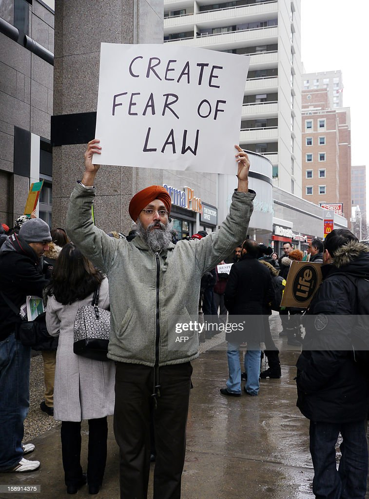 A man holds a sign as people demonstrate in Toronto, Ontario, on January 3, 2013 to press the Indian government for action following the gang-rape and murder of a student last month in New Delhi. The group delivered a letter with more than 200 signatures to the Indian consulate. Toronto, is Canada's biggest city, and is home to some 170,000 people of Indian origin.