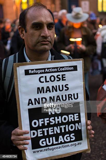 A man holds a sign at a candle light vigil in memory of asylum seeker Hamid Kehazaei held in Sydney Town Hall Hamid was declared braindead because of...