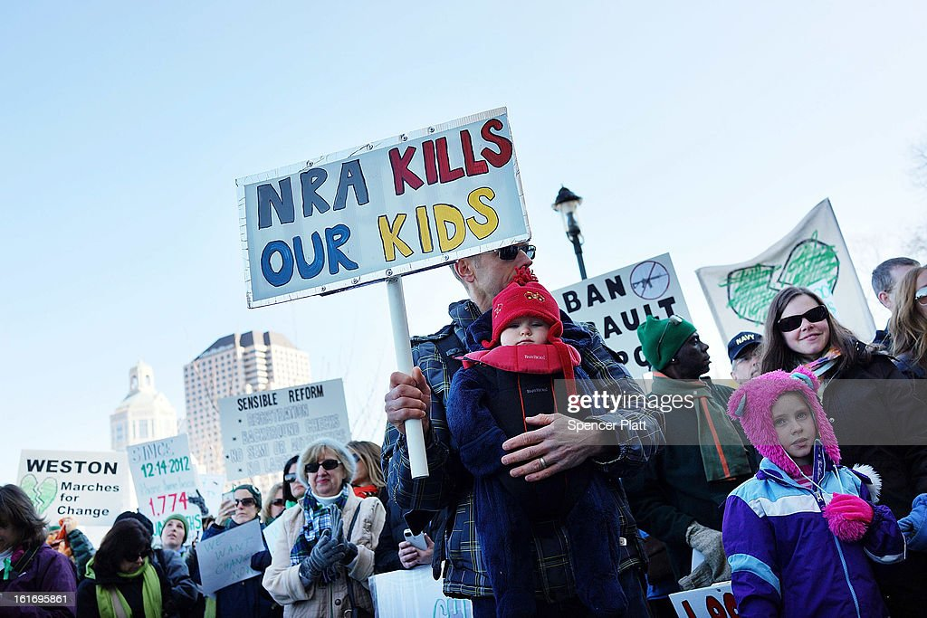 A man holds a sign during a rally at the Connecticut State Capital to promote gun control legislation in the wake of the December 14, 2012, school shooting in Newtown on February 14, 2013 in Hartford, Connecticut. Referred to as the 'March for Change' and held on the two-month anniversary of the massacre in Newtown, Connecticut, participants called for improved gun safety laws. Among the safety measures being demanded are for universal background checks, more work within the mental health community and restricting high-capacity magazines.