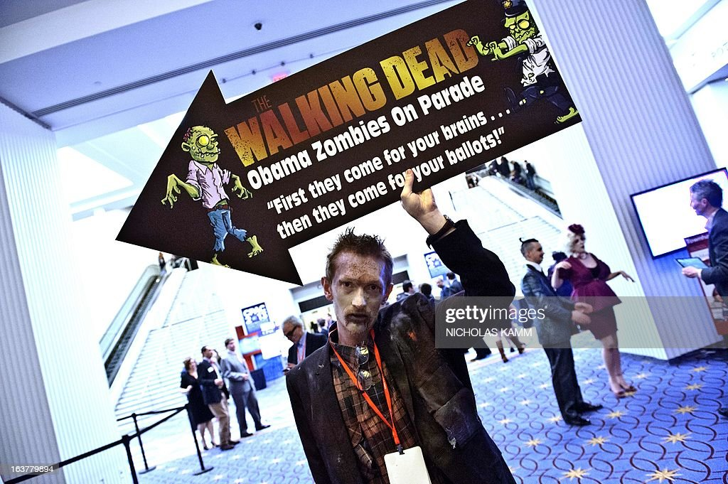 A man holds a sign for a show titled Walking Dead - Obama Zombies on Parade at the Conservative Political Action Conference (CPAC) in National Harbor, Maryland, on March 15, 2013. AFP PHOTO/Nicholas KAMM