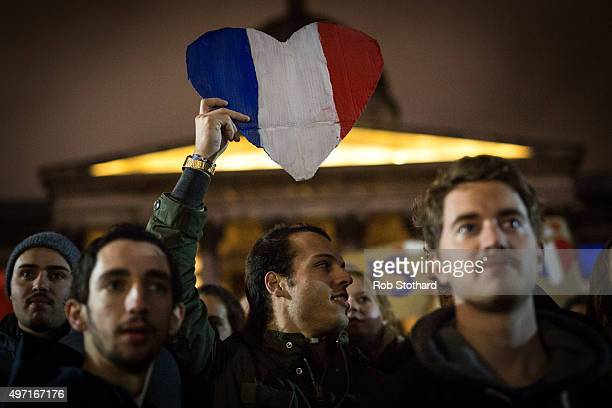A man holds a sign in the shape of a heart with the french flag as people hold a vigil for victims of the Paris terrorist attacks in Trafalgar Square...