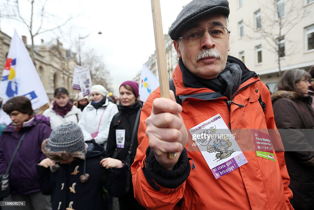 A man holds a sign, on January 23, 2013, in Paris, as he and other teachers take part in a nationwide strike and protest action against a proposed reform to increase the class time of primary school students. The strike and rally was called by French educational trade unions to protest a reform proposition by France's Education Minister, planned for the 2013-2014 schoolyear, which foresees an increase of class time in primary schools to 4.5 days a week and would affect both students and teachers.