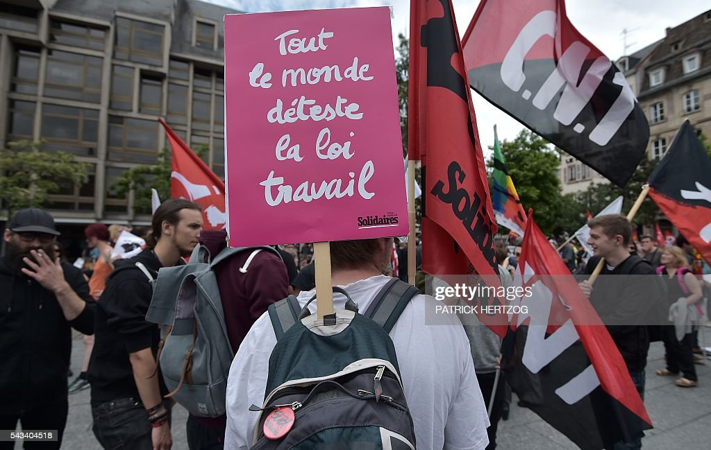 A man holds a sign reading 'Everybody hates the Labour law reforms' during a demonstration against controversial labour reforms, on June 28, 2016 in Strasbourg, eastern France. Unions have called repeated strikes and marches against controversial labour reforms, forced through by the government of Socialist President Francois Hollande. / AFP / PATRICK