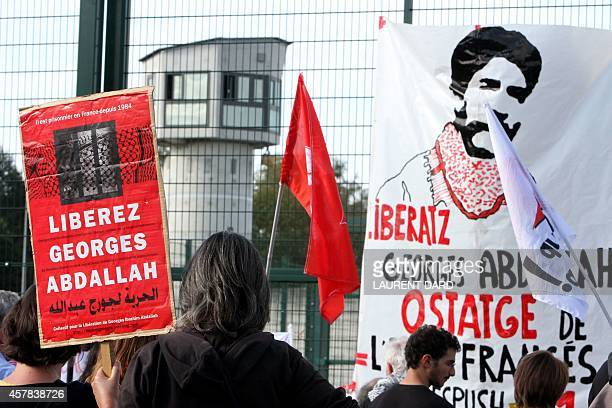 A man holds a sign reading 'Free Georges Abdallah' as demonstrators gather in front of the prison in Lannemezan southern France on October 25 to call...