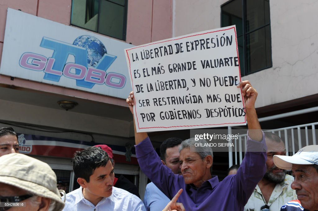 A man holds a sign reading 'Freedom of expression is the biggest bastion of freedom and can only be restricted by despotic governments' during a protest for the closure of opposition channel Globo TV in Tegucigalpa on May 25, 2016, on Journalis Day. Protesters accused the government of taking reprisals for the corruption denunciations the channel has done. / AFP / ORLANDO