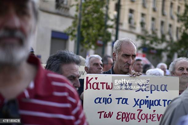A man holds a sign reading 'hands off the money to workers' as pensioners gather against austerity measures on June 23 2015 in Athens Hopes that...