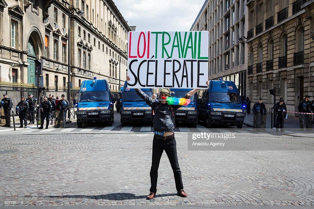 A man holds a sign reading in 'Work law treacherous' in front of French anti riot police during the protest against the 'Loi - El Khomri' in front of Invalides in Paris, France on May 03, 2016.