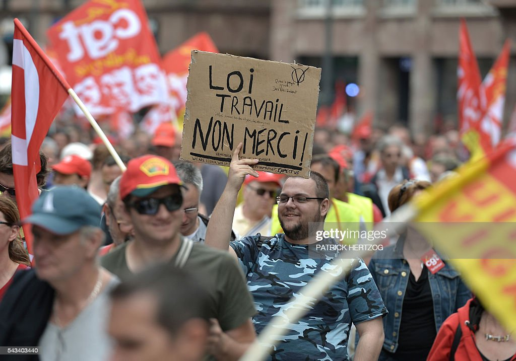 A man holds a sign reading 'Labour law, no thanks!' during a demonstration against controversial labour reforms, on June 28, 2016 in Strasbourg, eastern France. Unions have called repeated strikes and marches in opposition to the law, which seeks to bring down France's intractable 10-percent unemployment rate by making it easier to hire and fire workers. / AFP / PATRICK