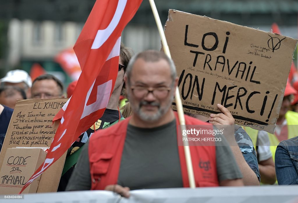 A man holds a sign reading 'Labour law, no thanks!' during a demonstration against controversial labour reforms, on June 28, 2016 in Strasbourg, eastern France. Unions have called repeated strikes and marches against controversial labour reforms, forced through by the government of Socialist President Francois Hollande. / AFP / PATRICK